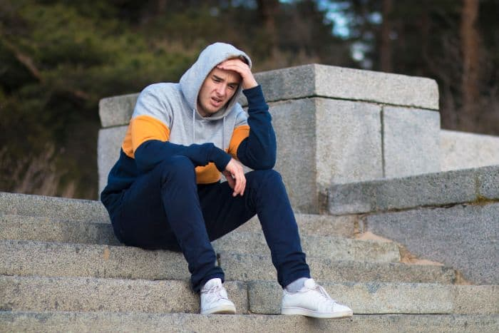 Sad man crying while sitting on steps in a hoodie