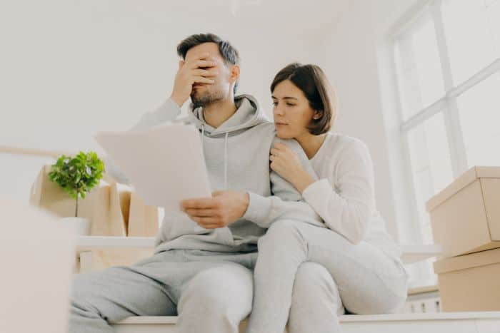 A frustrated man with a document in hand as the woman looks over from his shoulder what the document is about