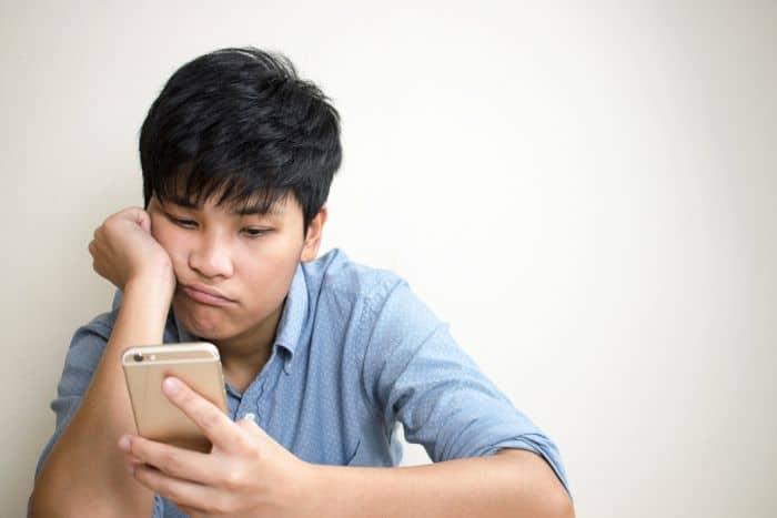 sad man checking phone