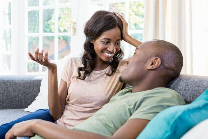 Young black couple talking to each other on a couch