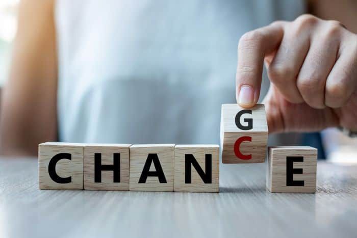Man holding a small wooden cube with 'C' at the bottom and 'G' in the front to spell 'Change' and 'Chance'