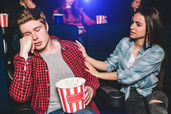 Woman waking up his sleeping boyfriend in a movie theatre