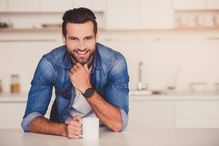 Attractive man drinking coffee in his kitchen