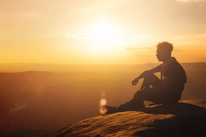 Man sitting on a hilltop at sunset and thinking