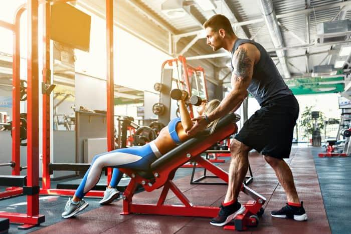 Man helping woman lift weights